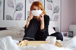 siedząca na łóżku kobieta w ciemnej piżamie jesiennej