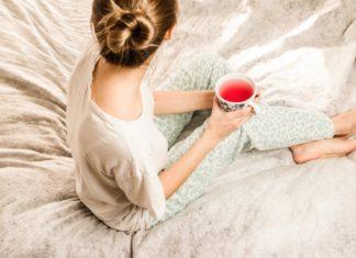 kobieta siedzi w piżamie z kubkiem jesienią lub zimą na łóżku